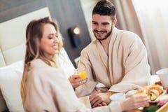 Gl?ckliches Paar, das im Luxushotelraum fr?hst?ckt lizenzfreie stockbilder