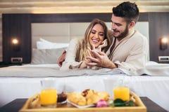 Gl?ckliches Paar, das im Luxushotelraum fr?hst?ckt lizenzfreie stockfotos