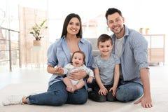 Gl?ckliches Paar mit den Kindern, die auf Boden sitzen Vater und Kinder mit Fahrr?dern stockbild
