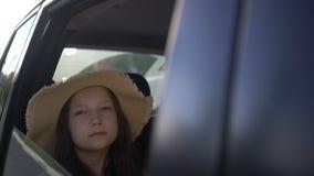 Gl?ckliches sch?nes M?dchen mit dem Strohhut, der in einen Autor?cksitz reist Autoreise-Konzept stock video
