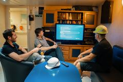 Gl?ckliches Team von Schiffsoffizieren sehen an Bord des Schiffes fern lizenzfreie stockbilder