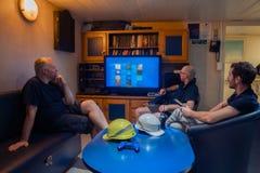 Gl?ckliches Team von Schiffsoffizieren sehen an Bord des Schiffes fern stockfotografie