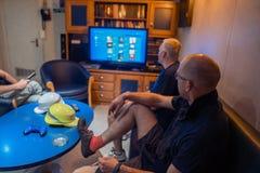 Gl?ckliches Team von Schiffsoffizieren sehen an Bord des Schiffes fern stockbilder