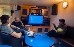 Gl?ckliches Team von Schiffsoffizieren sehen an Bord des Schiffes fern lizenzfreie stockfotografie