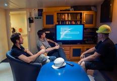 Gl?ckliches Team von Schiffsoffizieren sehen an Bord des Schiffes fern lizenzfreie stockfotos