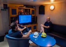 Gl?ckliches Team von Schiffsoffizieren sehen an Bord des Schiffes fern lizenzfreies stockfoto