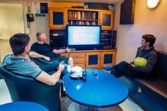 Gl?ckliches Team von Schiffsoffizieren sehen an Bord des Schiffes fern stockfoto