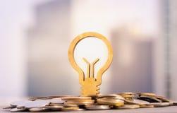 Gl?hlampe und Stapel M?nzen im Konzept von Einsparungen und von Geldwachsen oder von Energieabwehr lizenzfreie stockbilder
