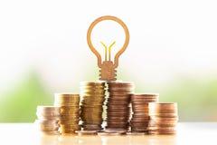 Gl?hlampe und Stapel M?nzen im Konzept von Einsparungen und von Geldwachsen oder von Energieabwehr stockbild