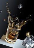 Glaçon éclaboussant dans des glas de liquide. Images libres de droits