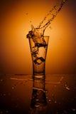 Glaçons éclaboussant dans la glace de l'eau Images libres de droits