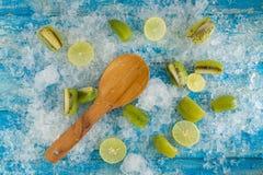 Glaçons et citron écrasés, kiwi, cuillère en bois sur le bleu de vintage Photographie stock libre de droits