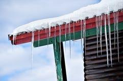 Glaçons fondant sur un toit en bois de chalet Image libre de droits