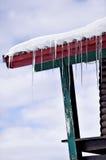 Glaçons fondant sur un toit en bois de chalet Photo stock