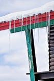 Glaçons fondant sur un toit en bois de chalet Photographie stock libre de droits