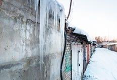 Glaçons sur la maison, garage dans la rue, grands glaçons d'hiver Photos libres de droits