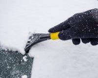 Glace éraflant sur le disque avant de voiture en hiver photos stock