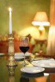 Glace avec du vin et la bougie à la table Images libres de droits