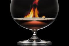 Glace avec le cognac sur un fond un incendie Photographie stock libre de droits