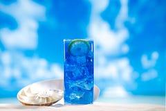 Glace bleue de neige fondue en verre sur le fond de plage de mer Image stock