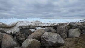 Glace bleue poussée contre un rivage rocheux Images stock