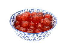 Glace cherries in a blue and white china bowl. Sticky red glace cherries in a blue and white porcelain bowl with a floral design, isolated on a white background Royalty Free Stock Photo