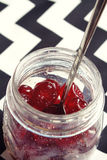Glace cherries in a vintage jar overhead. Close up of glace cherries in a vintage jar zig zag background Stock Image