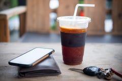Glace d'americano ou café noir avec les hommes portefeuille et la clé de voiture Image libre de droits