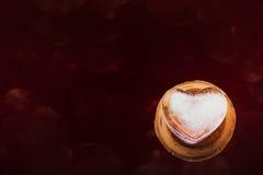 Glace de forme de coeur sur le mini vase cuit au four à argile et le fond rouge foncé Photographie stock libre de droits
