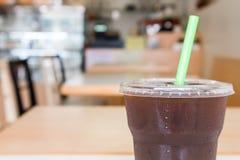 Glace de l'americano avec le fond de tache floue de boutique de café de café, Co noire Photographie stock