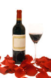 Glace de vin, bouteille et pétales roses Image libre de droits