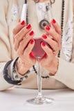 Glace de vin rouge dans des mains femelles Photos libres de droits