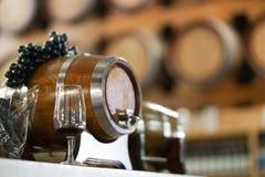 Glace de vin Un verre de vin rouge devant un baril de vin Vin image libre de droits