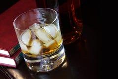 Glace de whiskey et d'un bon livre Photo libre de droits