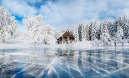 Glace et fissures bleues sur la surface de la glace Lac congelé sous un ciel bleu pendant l'hiver Cabine dans les montagnes photo libre de droits