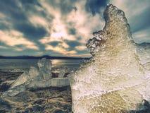 Glace fondant sur la plage sablonneuse Détail de banquise avec les fissures profondes à l'intérieur Photo libre de droits