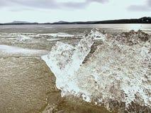 Glace fondant sur la plage sablonneuse Détail de banquise avec les fissures profondes à l'intérieur Image libre de droits
