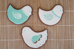 Glace-iced homemade cookies on beige background. Bird-shaped homemade cookies on beige background Royalty Free Stock Image