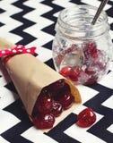 Glace körsbär i pappers- kotte på sparrebakgrund Royaltyfria Bilder