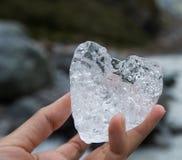 Glace naturelle de forme de coeur dans une main Photographie stock