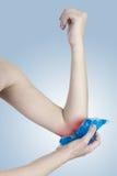 Glace sur un coude blessant gonflé. Photos libres de droits