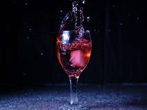 Glace tombant sur un verre avec la boisson qui se renverse et éclabousse photo stock