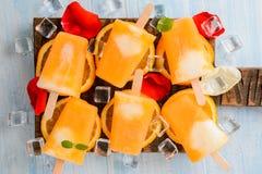 Glaces à l'eau congelées faites maison de crème glacée faites avec les oranges fraîches oragnic sur le fond en bois, images libres de droits