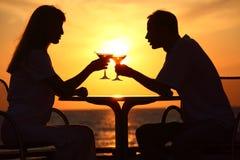 Glaces de taule de couples sur le coucher du soleil à l'extérieur Images stock