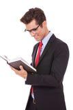 Glaces s'usantes d'homme d'affaires et affichage d'un livre Photos stock