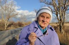 Glaces s'usantes se reflétantes d'une femme âgée Photographie stock