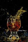 Glacez l'éclaboussement dans un verre sur le jaune photographie stock