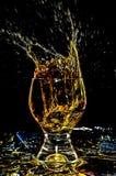 Glacez l'éclaboussement dans un verre sur le jaune 1 image stock