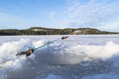 Glacez la canne à pêche avec la ligne à la glace près du trou, passe-temps Images libres de droits