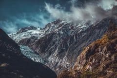 Glaciär och moln över ojämna berg fotografering för bildbyråer